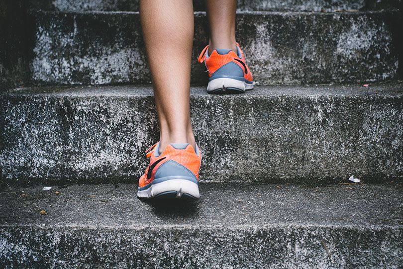 A woman's feet wearing tennis shoes climbing stairs.