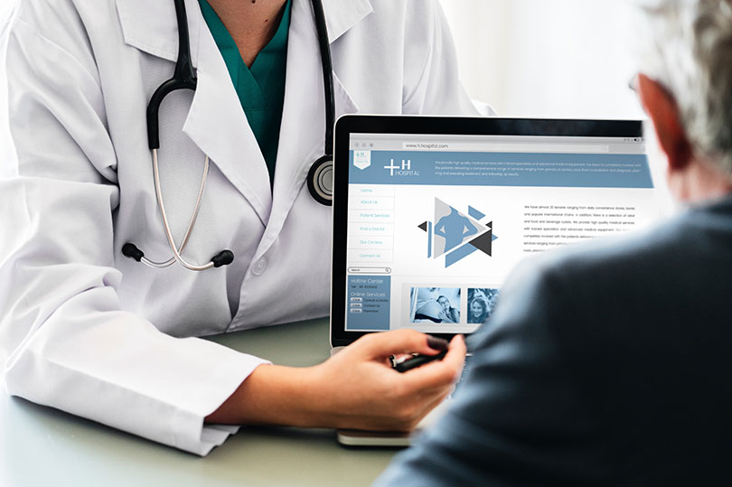 Doctor showing laptop image to a person wearing a black shirt.