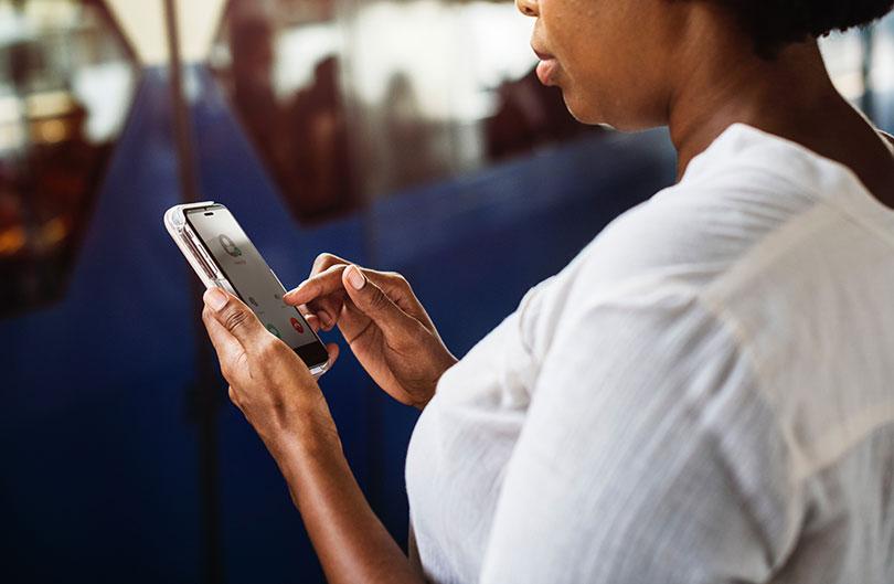 Young black woman checks her mobile phone.
