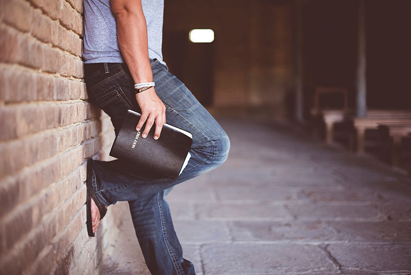 Man leaning against a brick wall holding a bible.