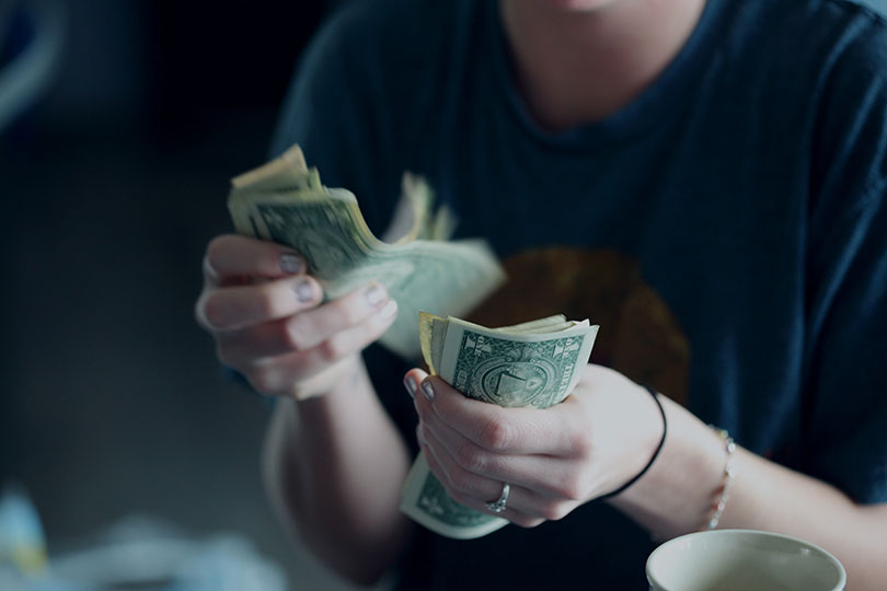 A pair of women's hands holding dollar bills.