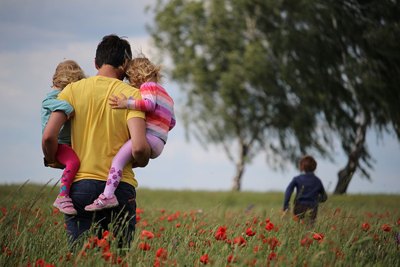 Man carries two small children while following a third in a field of tulips.