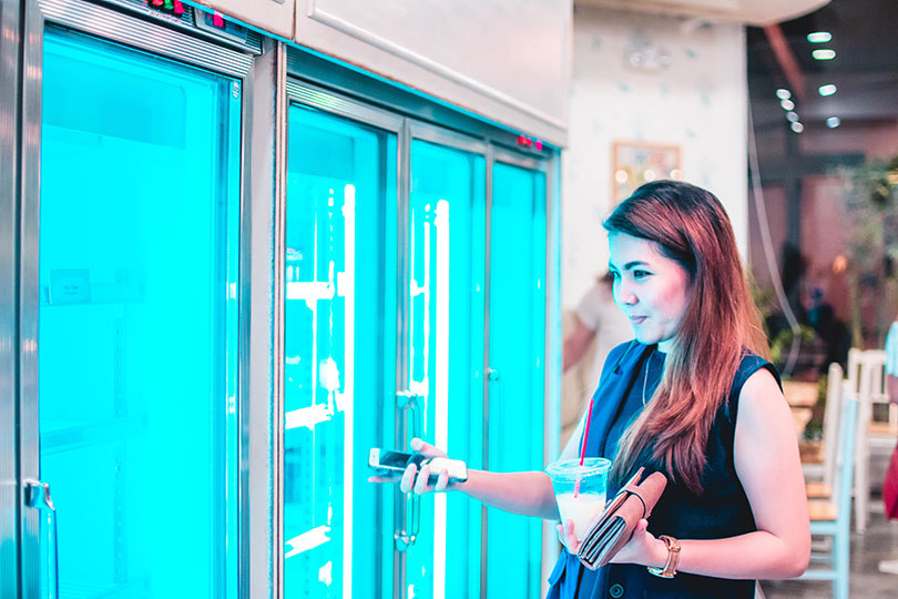 Woman looks inside cooler doors while shopping