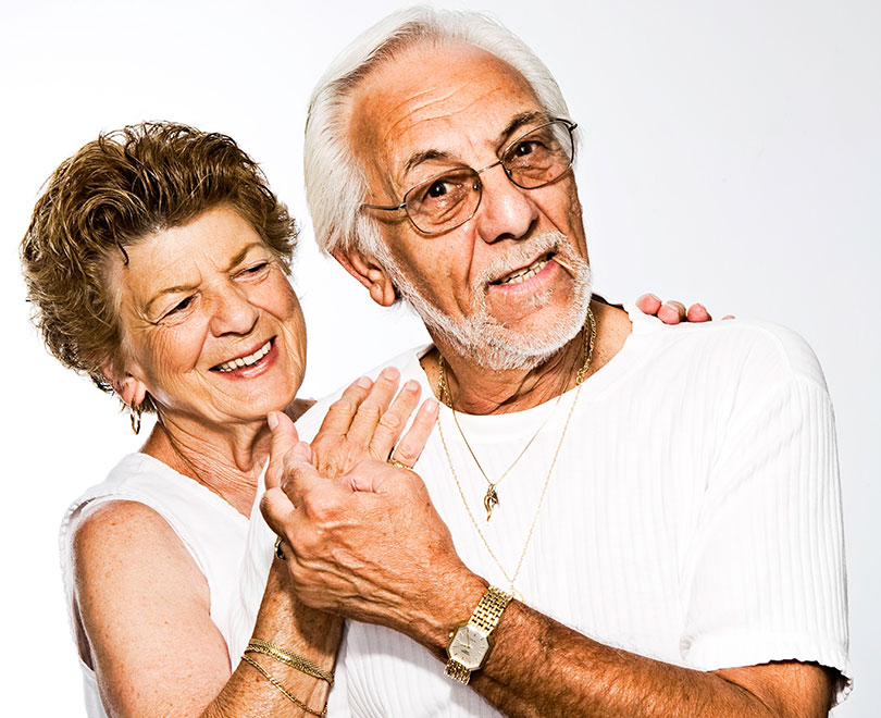 Mature couple smiling, in an embrace.