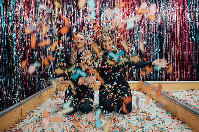 Two women having fun with confetti.