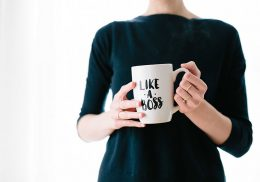 Torso of a woman holding a mug that reads like a boss