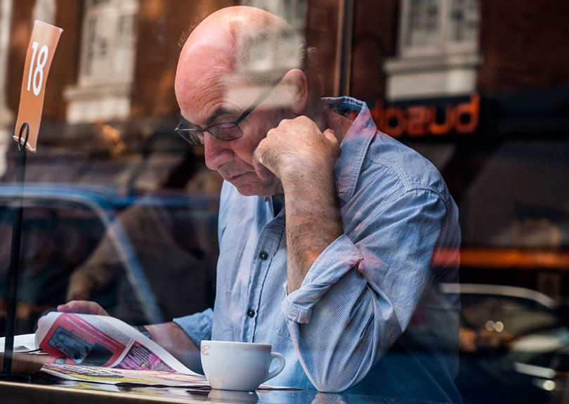 Mature man reads newspaper in a coffee shop.