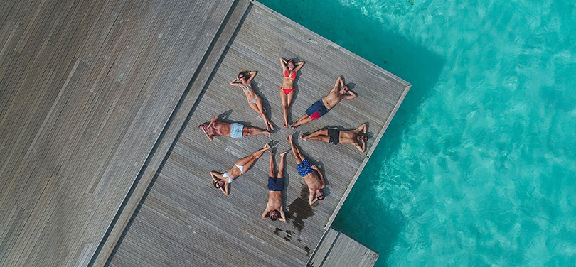 Young people sunbathe in a circle on a deck surrounded by crystal clear water.