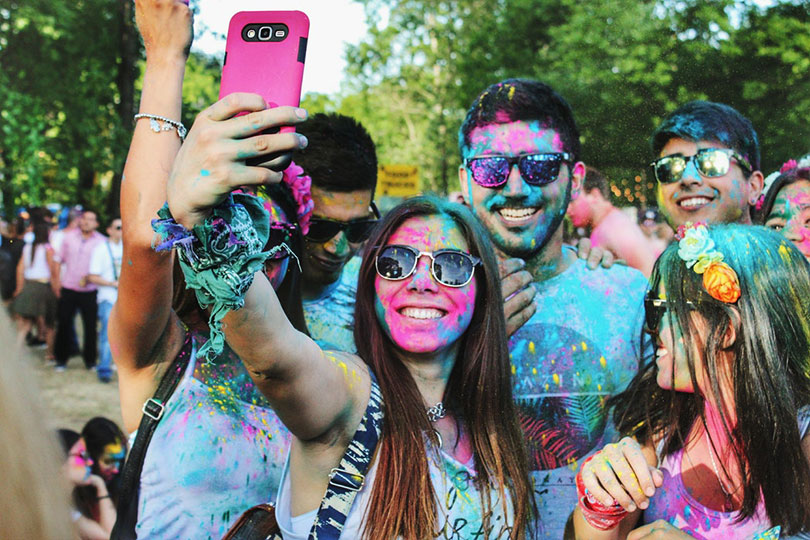 Group of young people taking a selfie at a color run race.