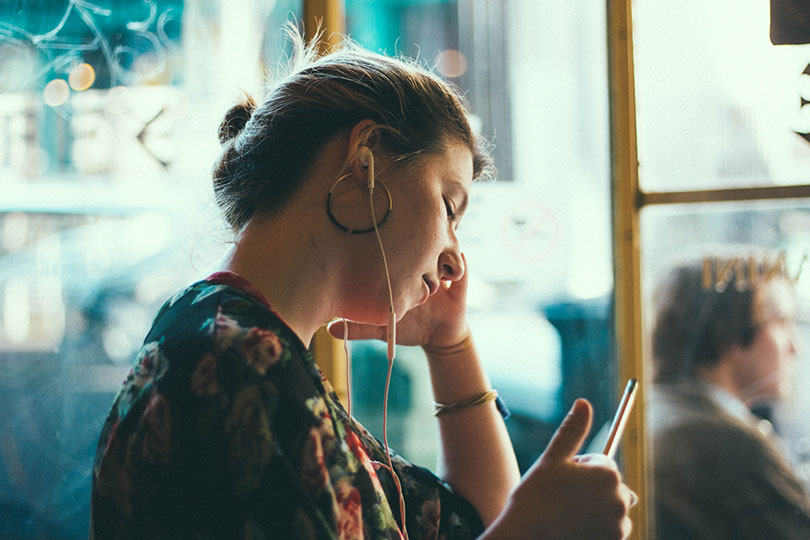 Woman wearing ear buds while holding a mobile phone.