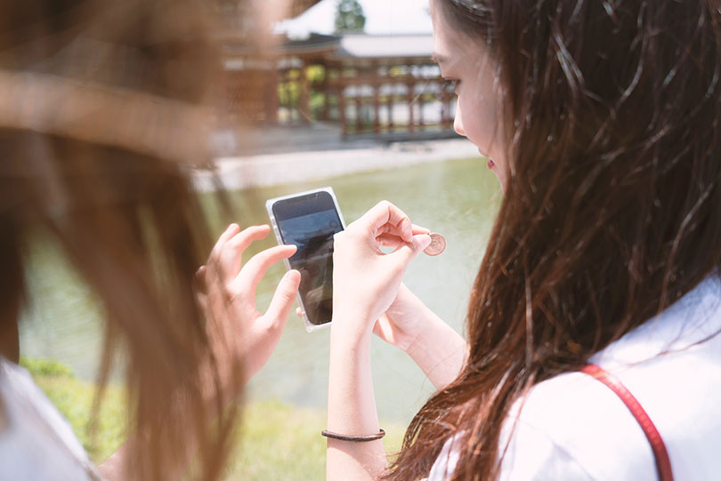 Young woman looks at image in phone.