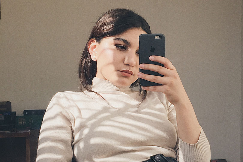 Women sitting on couch staring at her mobile phone.