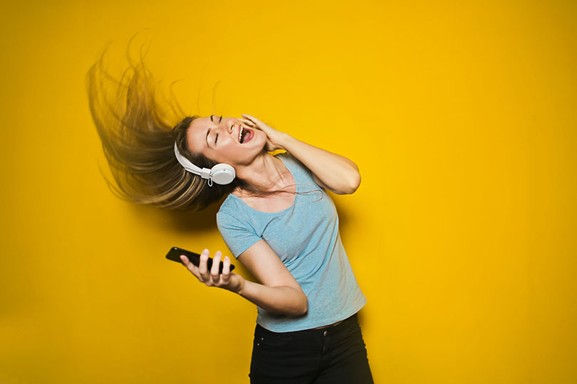 Young woman wearing headphones and holding a mobile phone dancing.