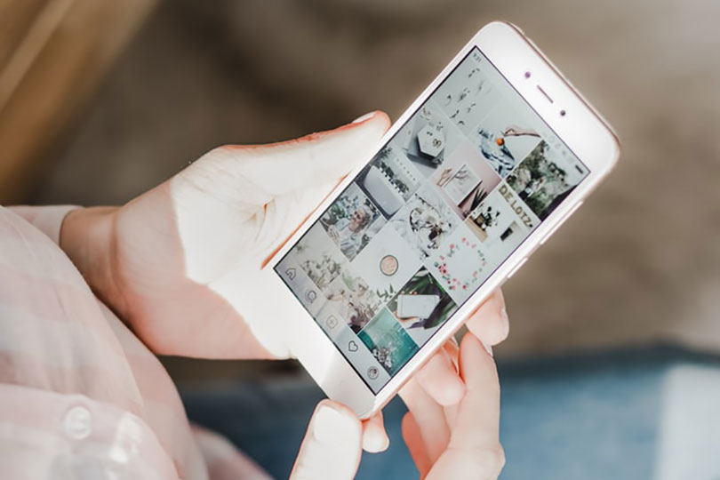 A woman holding a phone looking at an Instagram page.