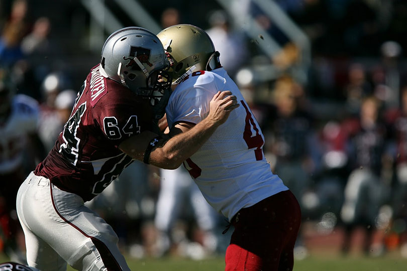 Football players battle for position.