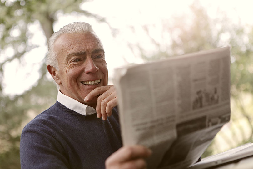 Older man smiling while reading the newspaper.