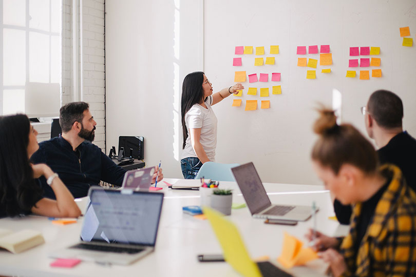 Woman putting sticky notes on whiteboard while in meeting with peers