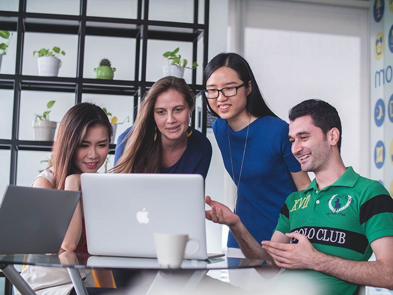 Three women and a man look at computer screen smiling.