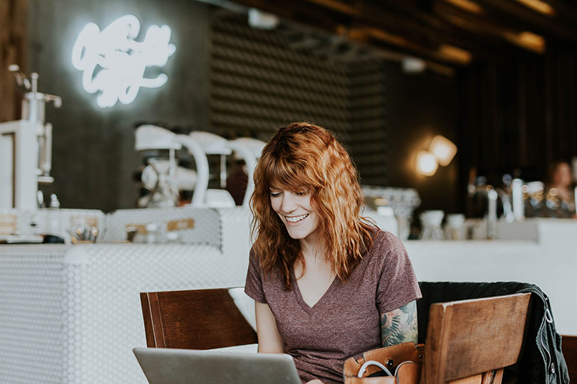 Woman sitting in a café looking at a laptop screen smiling.