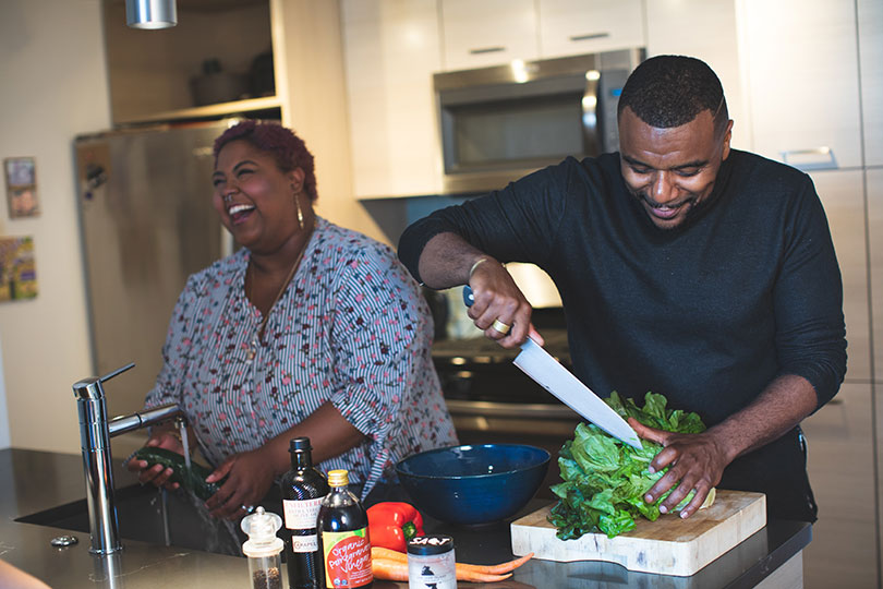 Couple smiles happily while meal prepping in family kitchen.