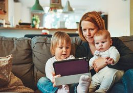 Mom sits on a couch with two babies and a tablet.