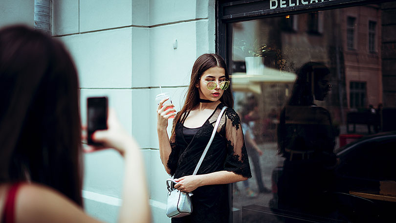Woman takes a picture of another woman using a mobile phone.