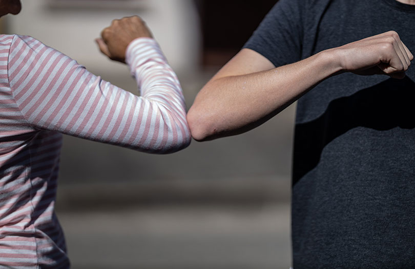 Two people bump elbows.