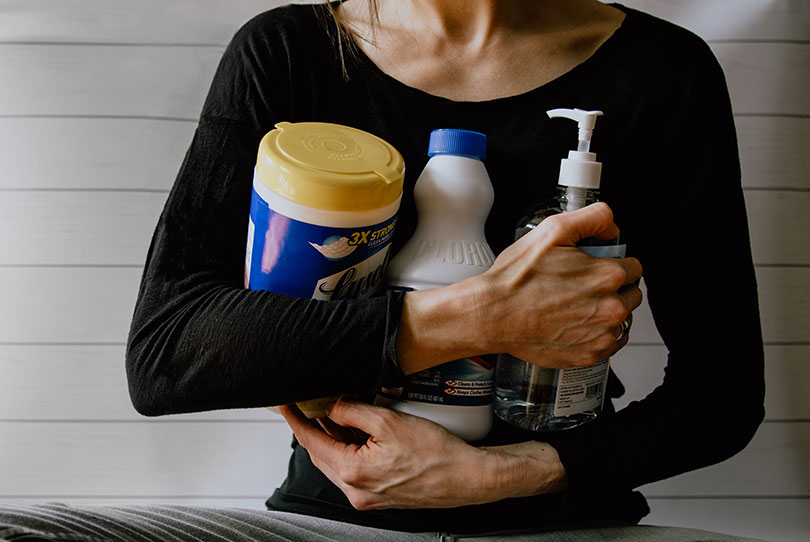 Woman holding cleaning supplies.