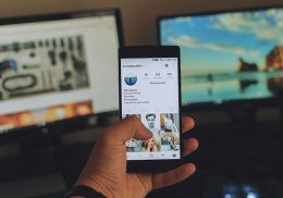 Man holds smartphone in hand with social media image on screen.