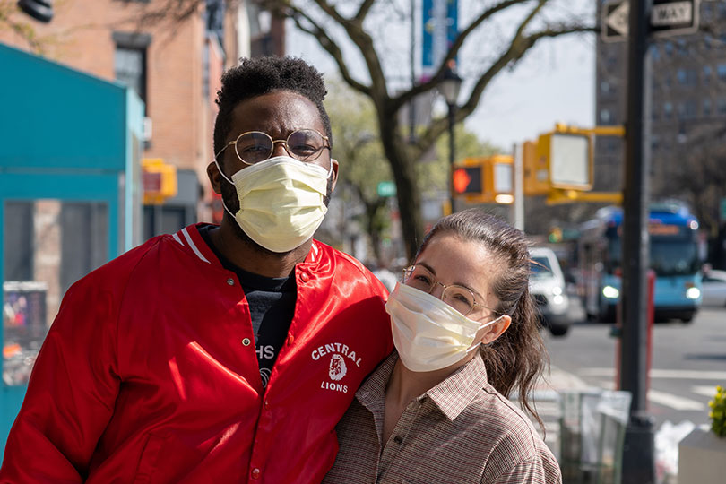 A couple wearing personal protection masks embrace in public