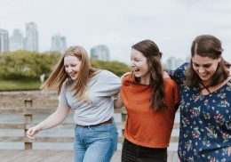 Three young women walking outdoors together.