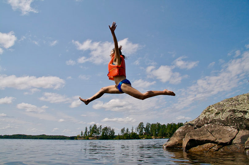Woman jumping off rocks into water.