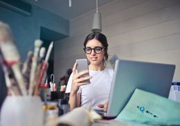 Woman sitting in front of laptop and holding smartphone.
