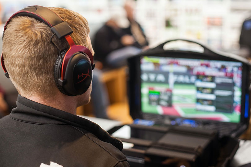 Man watching esports on a laptop and wearing headphones.