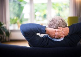 Middle aged man sitting on a couch, leaning back.