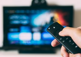 Hand holding a TV remote with screen in background.