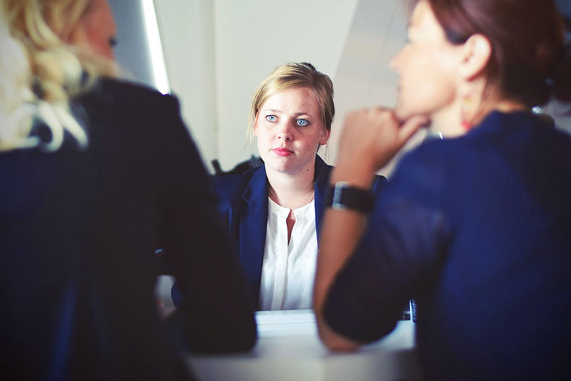 Woman sits across from two other women, listening