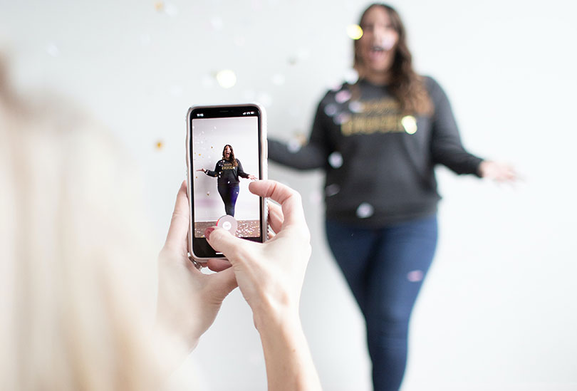 : A woman is being filmed by another woman, using a smartphone