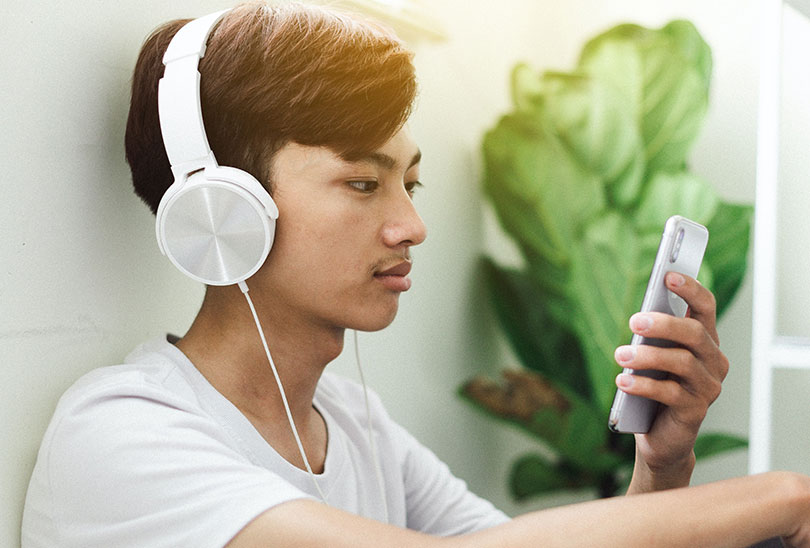 Young man wearing headphones and looking at smartphone screen
