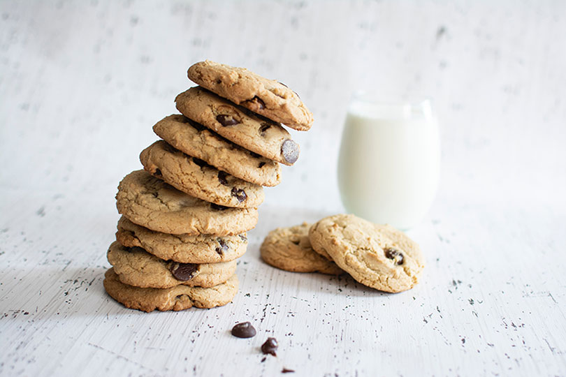 A stack of chocolate chip cookies and a glass of milk