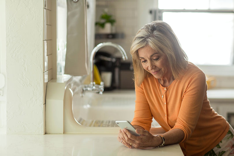 Middle aged woman looking at her smartphone while standing in a kitchen