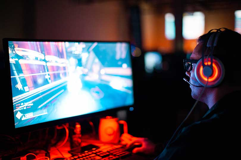 Man wearing headphones, looking at a screen, gaming.