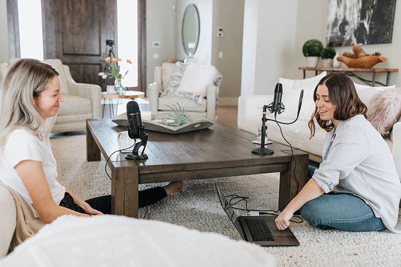 Two women sitting in a living room recording a podcast