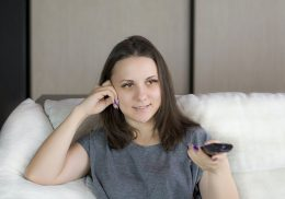 Woman sitting on a couch holding a TV remote