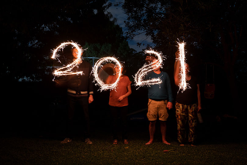 Four people write 2021 with sparklers
