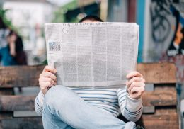 Man sitting on a bench reading a newspaper that covers his face.