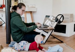 Mom works on a laptop on the floor with a baby by her side.