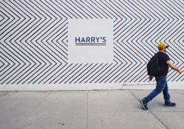 Man walking by a large poster advertising Harry's.