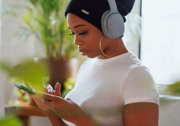 A woman wearing headphones while using a mobile phone